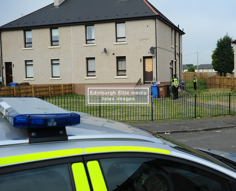 Pictured: police stand guard outside the house in Mayfield, Armadale this morning where windows were broken and a car was set alight as an angry crowd of locals jostled with a heavy police presence on Tuesday night after allegations against a resident.<br /> <br /> © Dave Johnston / EEm
