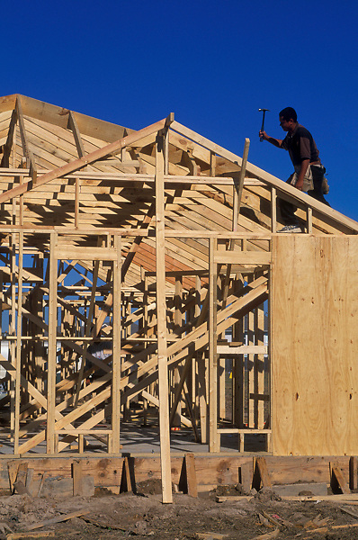 Stock photo of a man working on the roof of a framed in structure
