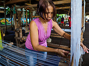 20 JANUARY 2018 - CAMALIG, ALBAY, PHILIPPINES: Genevieve Moya uses a loom to weave into placemats and table runners to sell to tourists at the Barangay Cabangan evacuee shelter in a school in Camalig. She makes the placemats and table runners at her home and brought her supplies with her to the shelter. There are about 650 people living at the shelter. They won't be allowed to move back to their homes until officials determine that Mayon volcano is safe and not likely to erupt. More than 30,000 people have been evacuated from communities on the near the Mayon volcano in Albay province in the Philippines. Most of the evacuees are staying at school in communities outside of the evacuation zone.   PHOTO BY JACK KURTZ