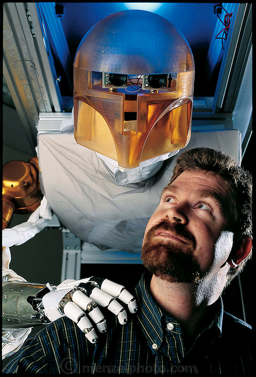 Feeling a hand resting on his shoulder, Robert J. Ambrose looks up to see a hovering Robonaut; the early prototype for the robotic astronauts his team is building for NASA at the Johnson Space Center in Texas. Intended to accompany astronauts into space, Robonaut will be especially important in emergencies. From the book Robo sapiens: Evolution of a New Species, page 128.