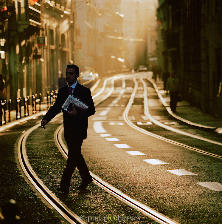 A businessman crosses the tram tracks of a central street, early in the morning in downtown Lisbon, Portugal