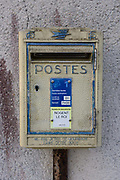 Postal box in rural village of Neron, Eure-et-Loir, France. The metal container for letters and cards remains unchanged since it was installed earlier in the 20th century. The letters F and R (France Postale) remains on the top and an advisory not to put newspapers in the box is seen at the bottom. A newer notice has been attached telling villagers when the daily and weekly collections are.