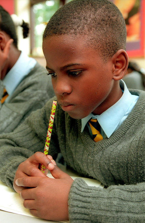 Young boy sitting in classroom at desk thinking and doing school work,