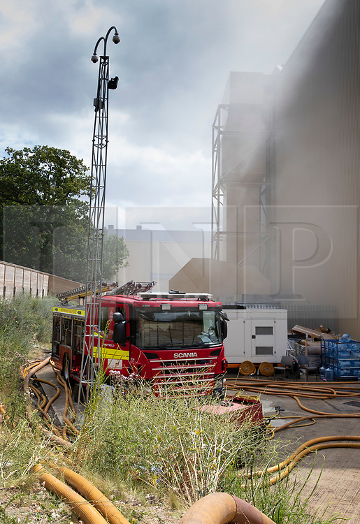 © Licensed to London News Pictures. 11/07/2019. Watford, UK. Fire engines and smoke can be seen at Stage P at the Warner Bros film studios at Leavesden near Watford as they deal with the aftermath of a blaze that started overnight. The fire service were called in overnight after a fire started in one of the studios. The Harry Potter series was filmed here. Photo credit: Peter Macdiarmid/LNP