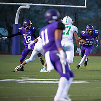 Lance Evans #12 releases his block as Rudy Romero #25 runs for a 5 Yd gain. Miyamura High School played against the Albuquerque Bulldogs Saturday night in a losing effort. The Bulldogs won 35-20 in Gallup, NM.
