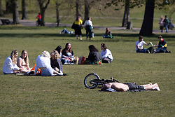 © Licensed to London News Pictures. 23/04/2021. London, UK. Members of the public relax and enjoy the sunny weather in Greenwich Park in south east London. Temperatures are expected to rise with highs of 16 degrees forecasted for parts of London and South East England today . Photo credit: George Cracknell Wright/LNP