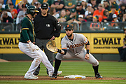 San Francisco Giants first baseman Brandon Belt (9) attempts to tag Oakland Athletics right fielder Matt Joyce (23) out at first base at Oakland Coliseum in Oakland, California, on July 31, 2017. (Stan Olszewski/Special to S.F. Examiner)