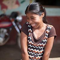 A young Q'eqchi girl laughs outside her school in Concepción Actelá, Alta Verapaz.
