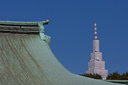 Docomo Tower seen behind the roof of Meiji Shrine, Yoyogi, Tokyo, Japan. Monday January 9th 2012