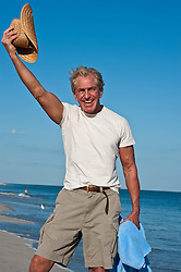 older man waving a hat while at the water's edge, Jones Beach, NY