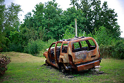 27 August 2014. Lower 9th Ward, New Orleans, Louisiana.<br /> Hurricane Katrina 9 years later. A burned out wreck of a car languishes on a vacant lot as the area continues to struggle to recover from Hurricane Katrina.<br /> Photo; Charlie Varley/varleypix.com