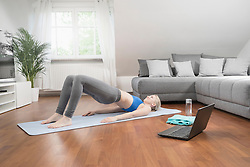 Young woman with laptop doing yoga on exercise mat in living room, Bavaria, Germany