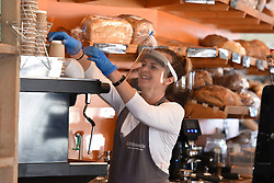 © Licensed to London News Pictures. 24/04/2020. Shoreham by Sea, UK. A shopkeeper wearing a protective face mask and gloves serves a customer at a cafe in Shoreham by Sea, during a pandemic outbreak of the Coronavirus COVID-19 disease.  Photo credit: Liz Pearce/LNP