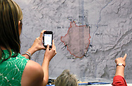A resident evacuated from the Yarnell Hill fire takes a photo of a map of the burned area at a community meeting in Prescott, Arizona July 2, 2013.   An elite squad of 19 Arizona firemen was  killed in the worst U.S. wildland firefighting tragedy in 80 years apparently outflanked and engulfed by wind-whipped flames in seconds, before some could scramble into cocoon-like personal shelters on June 30, 2013.  REUTERS/Rick Wilking (UNITED STATES)