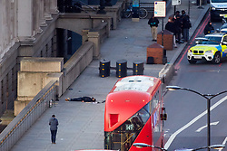 © Licensed to London News Pictures. 29/11/2019. London, UK.  A body, believed to be attacker Usman Khan, lies on the ground  following a suspected terror attack on London Bridge. Several people were stabbed, at least two fatally, before armed police shot the attacker dead.  Photo credit: Cliff Hide/LNP