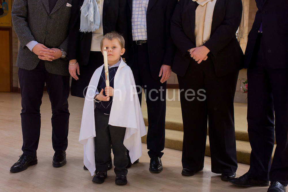 """Family and relatives after a 4 year-old's baptism ceremony in a local Catholic church. Standing in front of family members who tower above him, the lad proudly holds a large candle given to him by a witness after the baptism ceremony itself. The word baptism is a sacrament and an ordinance of Jesus Christ. In some denominations, baptism is also called christening but for others the word """"christening"""" is reserved for the baptism of infants."""