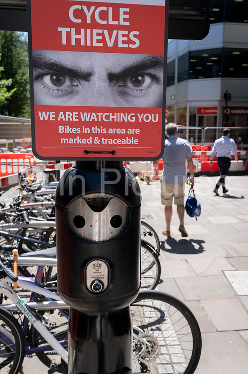 A crime prevention warning sign aimed at bike thieves, warns of being watched in an effort to cut the theft of property from cycling commuters, in the City of London, the capitals financial district, on 8th June 2021, in London, England.