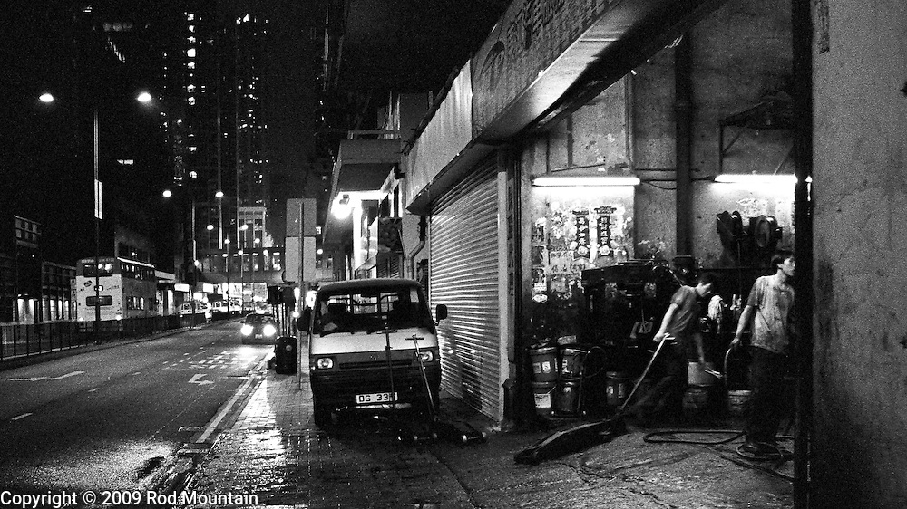 Two young men begin to put away their equipment as they close late into the evening at a local Hong Kong Garage. Photo: © Rod Mountain