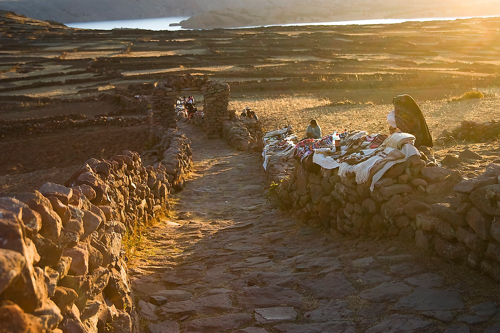 Local women display their textile handicrafts for sale along the stone path at the summit of Taquile Island on Lake Titicaca, Peru.