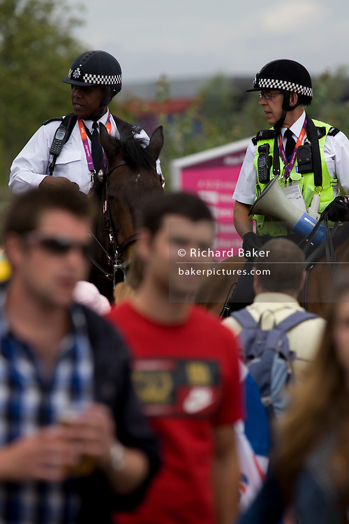 Mounted police officers help control crowds in horseback and provide security in the Olympic Park during the London 2012 Olympics. This land was transformed to become a 2.5 Sq Km sporting complex, once industrial businesses and now the venue of eight venues including the main arena, Aquatics Centre and Velodrome plus the athletes' Olympic Village. After the Olympics, the park is to be known as Queen Elizabeth Olympic Park.