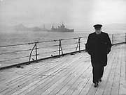 World War II: Winston Spencer Churchill (1874-1965) British statesman, in overcoat and hat and smoking a cigar, walking alone on the deck of HMS 'Prince of Wales' during the Atlantic Conference, 1941.