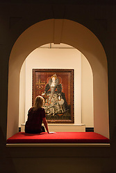 "© Licensed to London News Pictures. 09/10/2013. London, England. A museum worker sits in front of a paining of Queen Elizabeth I by an Unknown artist. Press preview of the exhibition ""Elizabeth I & Her People"" at the National Portrait Gallery which explores the remarkable reign of Elizabeth I through the lives and portraiture of her subjects. Exhibition runs from 10 October 2013 to 5 January 2014. Photo credit: Bettina Strenske/LNP"
