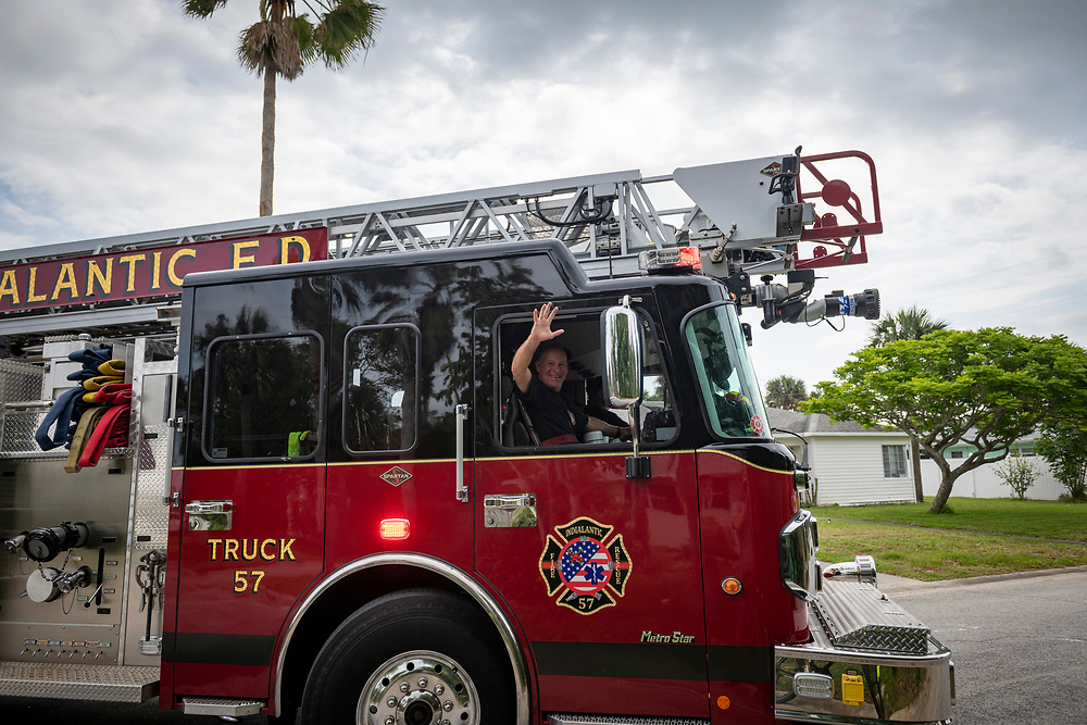 """A fireman waves from his truck during a neighborhood """"Stay at Home"""" parade in Indialantic, Florida (April 17, 2020)"""