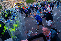 Glasgow, Scotland, UK. 15 May 202. Rangers football supporters  celebrating 55th league victory are cleared from George Square by police in riot gear on Saturday evening. In very violent scenes police were pelted with bottles and items from a nearby construction site as police pushed the supporters into the south west corner of the square. Pic; Police are confronted by angry Rangers fans. Iain Masterton/Alamy Live News.