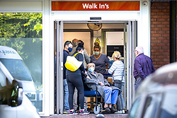 """© Licensed to London News Pictures . 10/08/2021. Wigan , UK . People stood waiting at the """" Walk In's """" [sic] entrance of Royal Albert Edward Infirmary A&E in Wigan . Yesterday and today (9th and 10th August 2021) the hospital has published advice for people to stay away unless facing an emergency , as officials describe services as being """"very busy"""" . Photo credit : Joel Goodman/LNP"""