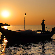 Silhouette of fisherman on boat at the dusk. Palm trees on background