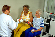Women age 70 and age 80 working out with trainer age 25 at Lynnwood Recreation Center.  St Paul Minnesota USA