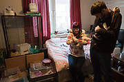 Kirkcaldy, Fife, Scotland: Ebony and her friend Ethan, holding some of her rats and rabbits. Ebony lives, in a small flat, with a total of 38rodents and small animals all told. Ebony volunteers on occasion during weekends at the nearby Linton Lane Community centre, serving drinks and food to the ever increasing numbers of local people who rely on the centre for their needs.<br /><br />Kirkcaldy is one of the poorest areas in Scotland with staggeringly high numbers of child poverty. Many disadvantaged families, and vulnerable people, and over a thousand children are surviving below the breadline in Kirkaldy East, that is 40%. Voluntary organisations and foodbanks give over a thousand food parcels a month, several times more than a few years ago. The Conservative government's policy of austerity together with the new 'Universal Credit' system which replaced six other benefits, makes millions of people poorer, many hundreds of thousands on the poverty line or below. Whilst people overall voted strongly against Brexit in Scotland, in other parts of the country, poorer constituencies voted largely for Brexit, in a vote against the City of London.