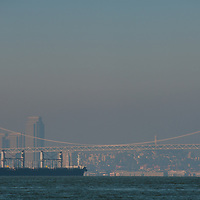 Container ships anchor in San Francisco Bay, waiting to load cargo at docks in either Oakland or San Francisco. Behind are downtown San Francisco and the Bay Bridge.