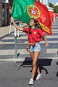 Portuguese supporter celebrating with national flag in a street in Lisbon. Portugal's national squad won the Euro Cup the day before, beating in the final France, the organizing country of the European Football Championship, in a match that ended 1-0 after extra-time.