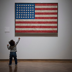 "© Licensed to London News Pictures. 19/09/2017. London, UK. A young visitor views ""Flag"", 1958, by Jasper Johns.  Preview of a landmark exhibition by Jasper Johns RA called ""Something Resembling Truth"" at the Royal Academy of Arts in Piccadilly.  Sculptures, drawing, prints plus new works are on display 25 September to 10 December 2017.   Photo credit : Stephen Chung/LNP"