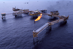 Stock photo of a complex of offshore petroleum production platforms with gas flare burning off waste gas off of the coast of Brunei in the South China Sea.