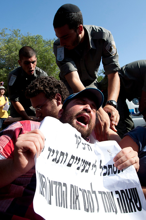 Israeli border police officers scuffle with protesters as they block the main entrance to Israel's Parliament building, the Knesset in Jerusalem, during a demonstration against The National Housing Committee's bill, on August 3, 2011. Over the past three weeks, Israelis have set up tent camps in cities throughout the country, and organized protest marches and demonstrations for lower housing and property prices in Israel and against social inequalities and the high cost of living.