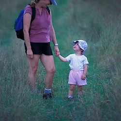 East Montpelier, VT. A mother and daughter  walk in a field on the Mallory Brook property.