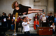 "A young magician performs a levitation trick using a lady assistant, in front of a crowd in Covent Garden's Piazza, London. Saying abracadabra or a similar explanation to wow his surrounding audience, the man stands beneath the raised woman, lying horizontally in mid-air. Levitation (from Latin levitas ""lightness"") is the process by which an object is suspended by a physical force against gravity, in a stable position without solid physical contact."