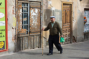 Local man walking with stick in Avila, Spain