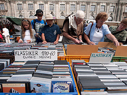 People browsing second hand movies at outdoor weekend flea-market beside Museumsinsel or Museums Island in Mitte Berlin Germany