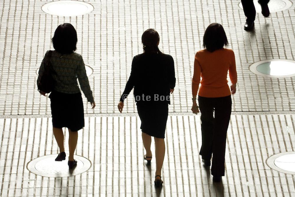 three businesswomen walking up to a businessman