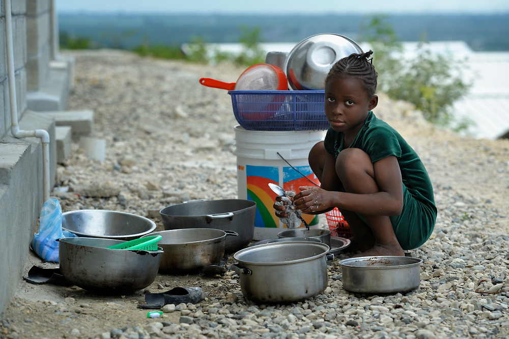 """A girl washes dishes in a model resettlement village constructed by the Lutheran World Federation in Gressier, Haiti. The settlement houses 150 families who were left homeless by the 2010 earthquake, and represents an intentional effort to """"build back better,"""" creating a sustainable and democratic community."""