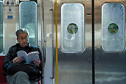 Man reading on an Odakyu Line train in rural Kanagawa, Japan. Saturday December 19th 2015