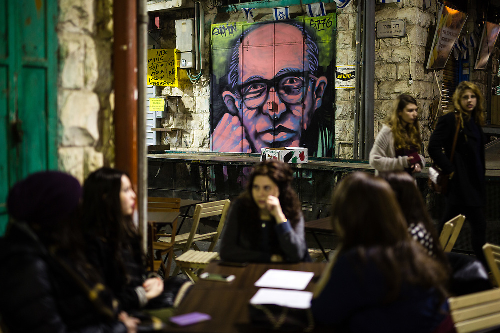 Israeli women enjoy at a local bar as they sit in front of a graffiti depicting the late Israeli Prime Minister Menachem Begin which was painted over a closed shutter at the Mahane Yehuda Market, often called 'The Shuk' in Jerusalem, Israel, on February 24, 2016.