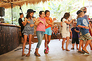 """Primary school students enjoying end of week song, dance, charade drama session<br /><br />The Green School (Bali) is one of a kind in Indonesia. It is a private, kindergarten to secondary International school located along the Ayung River near Ubud, Bali, Indonesia. The school buildings are of ecologically-sustainable design made primarily of bamboo, also using local grass and mud walls. There are over 600 students coming from over 40 countries with a percentage of scholarships for local Indonesian students.<br /><br />The impressive three-domed """"Heart of School Building"""" is 60 metres long and uses 2500 bamboo poles. The school also utilizes renewable building materials for some of its other needs, and almost everything, even the desks, chairs, some of the clothes and football goal posts are made of bamboo.<br /><br />The educational focus is on ecological sustainability. Subjects taught include English, mathematics and science, including ecology, the environment and sustainability, as well as the creative arts, global perspectives and environmental management. This educational establishment is unlike other international schools in Indonesia. <br /><br />Renewable energy sources, including solar power and hydroelectric vortex, provide over 50% of the energy needs of the school. The school has an organic permaculture system and prepares students to become stewards of the environment. <br /><br />The school was founded by John and Cynthia Hardy in 2008."""