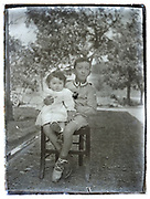 young boy with toddler sister posing 1900s France