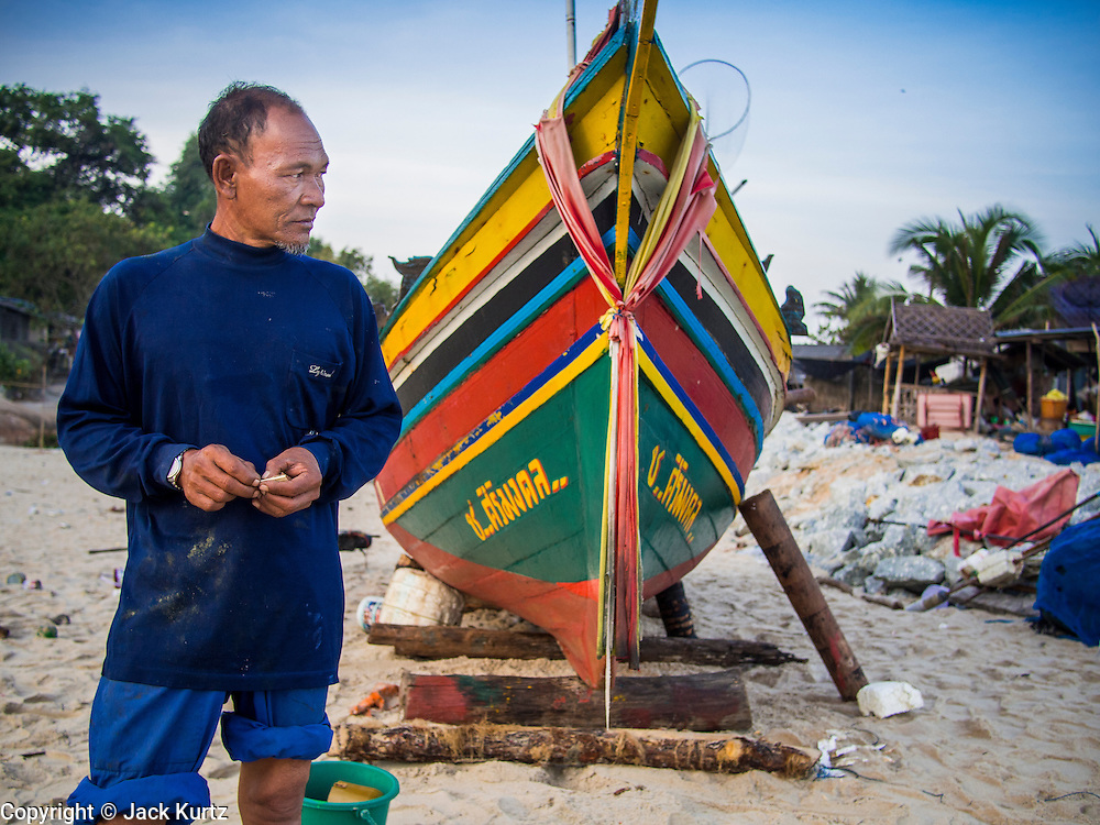 07 FEBRUARY 2014 - KAO SENG, SONGKHLA, THAILAND:  A fisherman next to his boat in Kao Seng. Kao Seng is a traditional Muslim fishing village on the Gulf of Siam near the town of Songkhla, in the province of Songkhla. In general, their boats go about 4AM and come back in about 9AM. Sometimes the small boats are kept in port because of heavy seas or bad storms.     PHOTO BY JACK KURTZ
