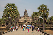 Tourists, guides and visitors walk along the stone walkway surrounding Ankor Wat temple complex in Krong Siem Reap, Cambodia. Angkor Wat is a temple complex in Cambodia and the largest religious monument in the world, with the site measuring 162.6 hectares. It is Cambodia's main tourist destination.(photo by Andrew Aitchison / In pictures via Getty Images)