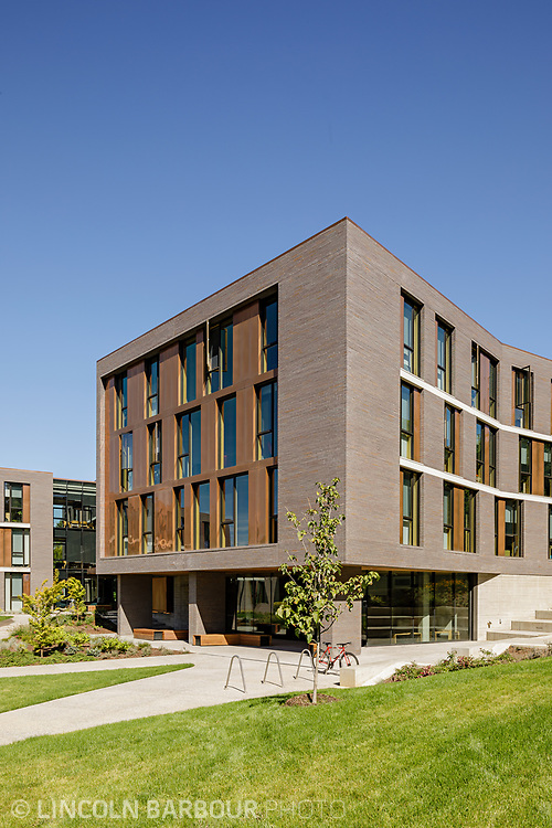 A vertical view of Trillium Residence Hall showing some of the landscaping in front and blue skies overhead.